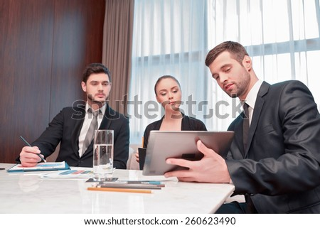 Getting varied input for a dynamic strategy. Three serious business people in formal wear looking at the digital tablet together - stock photo