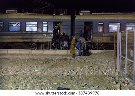 GEVGELIJA, MACEDONIA - FEBRUARY 11, 2016 : Immigrants and refugees from Middle East and North Africa boarding train in refugee transit camp.