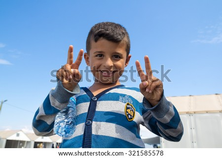 GEVGELIJA, MACEDONIA: SEPTEMBER 11, 2015: Immigrants and refugees from Middle East and North Africa in UNHCR camp. Little boy posing for camera. - stock photo