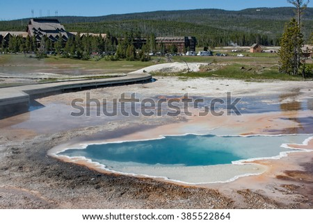 Geyser basin at the Old Faithful tourist center in Yellowstone National Park in Wyoming. Clear hot water springs and a boardwalk in the the Geyser basin. - stock photo