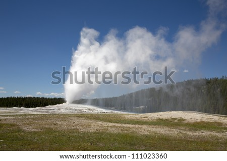 Geyser Old Faithful, in Yellowstone park, USA, erupting water and steam - stock photo