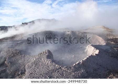 Geyser with mud vapor above in the natural reserve Reserva de Fauna Andina Eduardo Avaroa in Bolivia - stock photo
