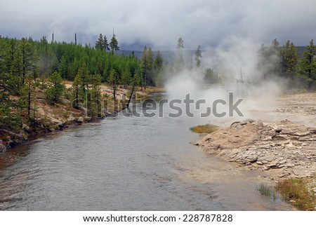Geysers by a river, Yellowstone, Wyoming, USA. - stock photo