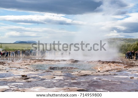 GEYSIR, ICELAND - JULY 28, 2017. End of eruption of Strokkur geyser, observed by many tourists,on day with remarkable cloudscape.
