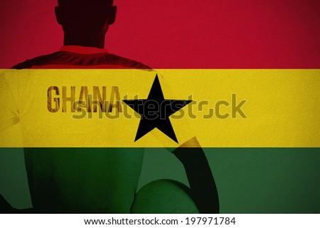 Ghana football player holding ball against ghana national flag - stock photo