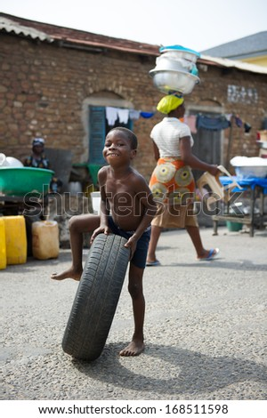 GHANA - MARCH 2, 2012: Unidentified Ghanaian boy plays with a car tire on the street in Ghana, on March 2nd, 2012. People in Ghana suffer from poverty due to the slow development of the country - stock photo