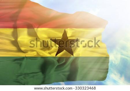 Ghana waving flag against blue sky with sunrays - stock photo