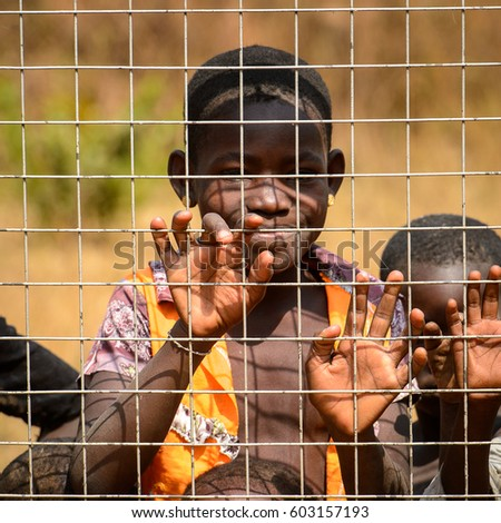 GHANI, GHANA - JAN 14, 2017: Unidentified Ghanaian little girl near the fence in a local village. Ghana people suffer of poverty due to the bad economy.