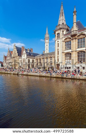 GHENT, BELGIUM - APRIL 6, 2008:  A lot of students sitting on the waterfront of river Leie along Graslei street