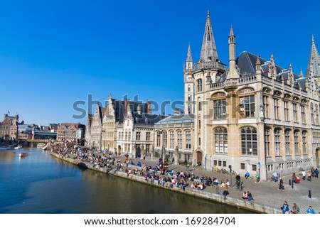 GHENT, BELGIUM - 21 APRIL : Picturesque medieval buildings overlooking Leie river in Ghent, Belgium on 21 April 2013. People gathered on the banks of the river Leie enjoy a sunny Sunday afternoon.
