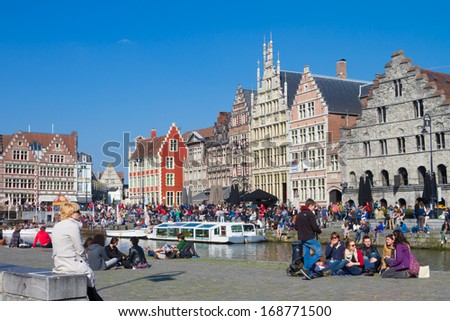 GHENT, BELGIUM - 21 APRIL : Picturesque medieval buildings overlooking the Graslei harbor in Ghent, Belgium on 21 April 2013. People gathered on banks of the river Leie enjoy a sunny Sunday afternoon. - stock photo