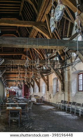 GHENT (GENT), BELGIUM - 02 MAY 2015: Interior inside the Great butchers hall (Groot Vleeshuis) - a former indoor meat market and the Guild house of butchers. Stone walls, cobbled floor and jamon.