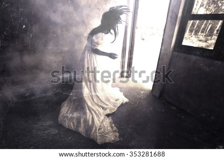 Ghost in Haunted House,Mysterious Woman in White Dress Standing in Abandon Building,Horror Background For Halloween Concept and Book Cover Ideas  - stock photo