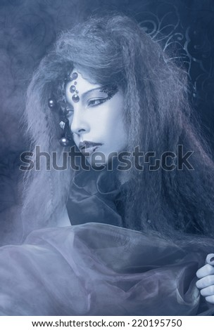 Ghost.Young woman with creative visage and mask posing in smoke
