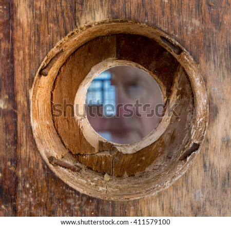 Ghostly face looking through a wooden door with small peep hole or viewing lens in the doorway