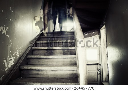 Ghostly figure standing on stairs holding doll  - stock photo