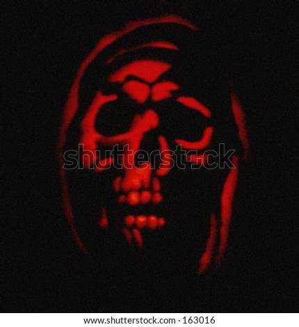 Ghostly image in red, carved Halloween pumpkin