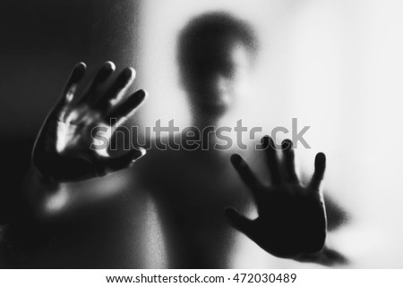 Ghosts hand silhouette behind the glass