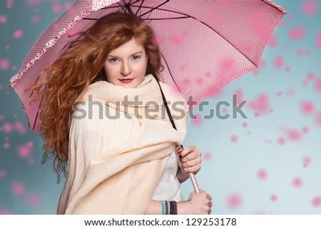 gi?nger girl holding a pink umbrella and looking at camera - stock photo