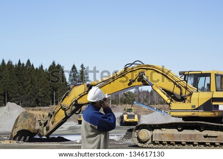 giant bulldozers, trucks and workers in action, gravel industry - stock photo