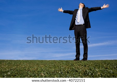 Giant businessman with arms outstretched on grassy hillside