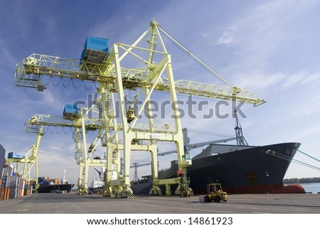 Giant container crane unloading a ship in a port - stock photo