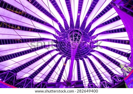 giant copula of sony center in berlin is made of white strips and is illuminated during night - stock photo