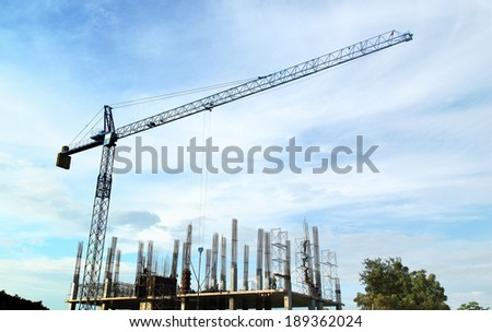 Giant crane lifting structure onto the building early in the morning - stock photo