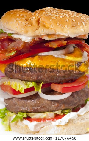 Giant double hamburger with tomato slices, cheese, cream cheese, bacon, egg, lettuce and onion in a white bread bun - stock photo