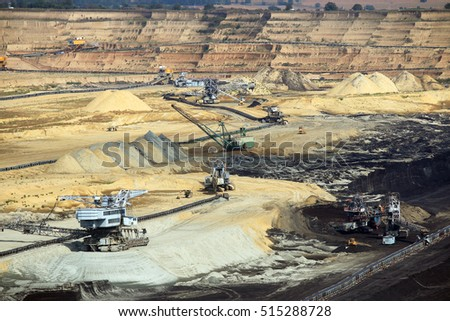 Giant excavators and heavy machinery working on opet pit coal mine