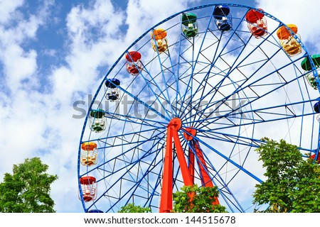 Giant ferris wheel against blue sky and white cloud which mean an amusement-park or fairground ride consisting of a giant vertical revolving wheel with passenger cars suspended on its outer edge - stock photo