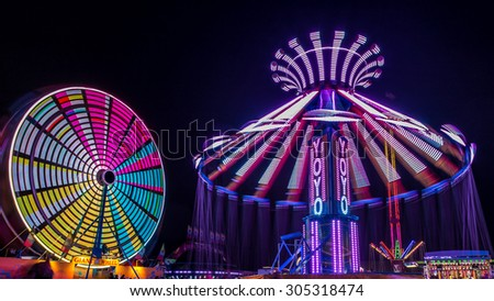 Giant Ferris Wheel and Yo-Yo amusement ride side by side in night time shot with long exposure. - stock photo