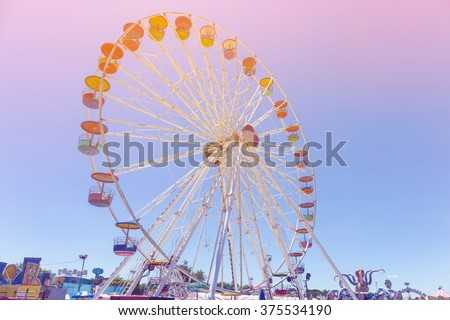 Giant ferris wheel in Amusement park with blue sky background pastel color tone - stock photo