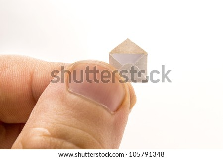 Giant fingers holds little open envelope with a letter inside - stock photo