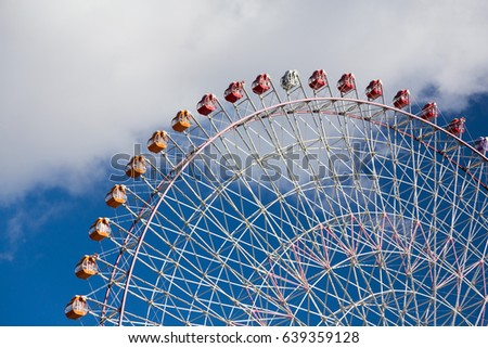Giant funfair ferris wheel with blue sky background