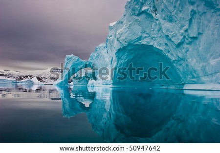 giant icebergs along the coastline of east greenland before sunrise - stock photo