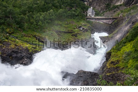 Giant Kjossfossen waterfall and station of famous Flam railway (Flåmsbana) in Flam valley, Norway - stock photo