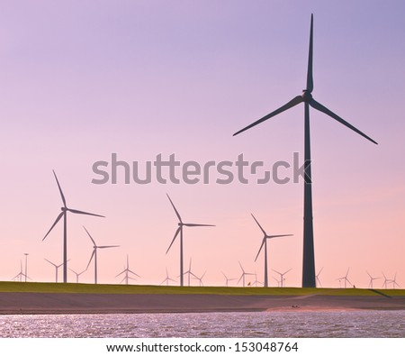 Giant 3 Megawatt Wind Turbines along the Sea Dike in the Netherlands seen from the Water - stock photo
