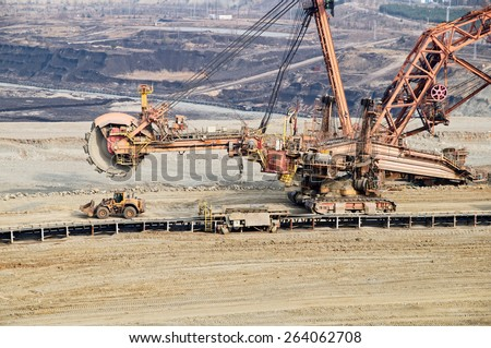 Giant mining excavator on the bottom surface mine. Brown coal deposits in the background. View from above. - stock photo
