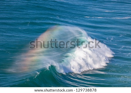 Giant Ocean Wave with Rainbow in Spray. Nazare, Portugal - stock photo