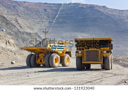 Giant Ore Trucks  in open pit mine - stock photo