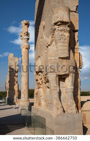 Giant Persian Lamassu and a remaining column representing typical Achaemenid architecture in the ruins of ancient Persepolis in Shiraz against Blue sky with white clouds.