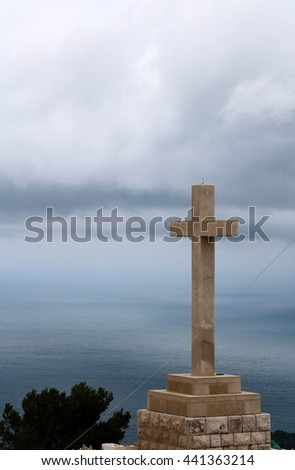 Giant stone cross in Dubrovnik in a gloomy and stormy weather, with dark clouds across the blackened Adriatic Sea - stock photo