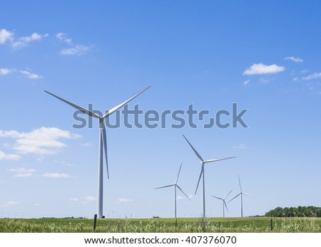 Giant turbines powered by the wind stand tall as they disappear into the distance in a field in Ontario Canada. - stock photo