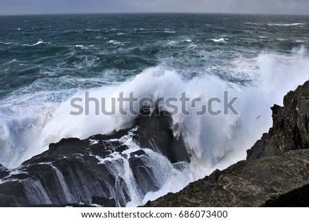 Giant Waves Nature Show crashing against dark colored cliffs, Meirás, A coruna, Galicia, Spain, raising a white foam dozens of meters against sky with stormy gray clouds in a dark green atlantic ocean