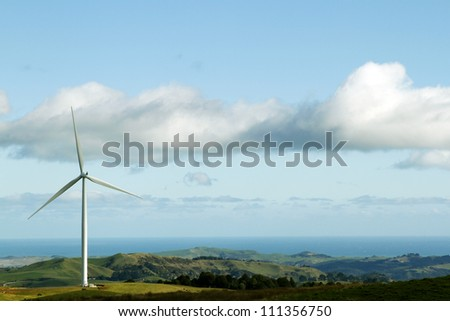 Giant wind turbine on hill. Coastline in background - stock photo