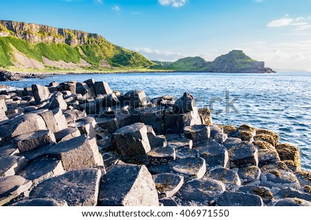Giants Causeway, unique geological hexagonal formation of volcanic basalt rocks and cliffs in Antrim County, Northern Ireland, in sunset light - stock photo