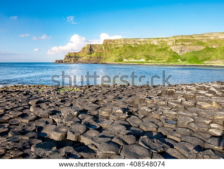 Giants Causeway, unique geological hexagonal formations of volcanic basalt rocks  and cliffs on Atlantic coast in County Antrim, Northern Ireland, in sunset light. UNESCO World Heritage site. - stock photo