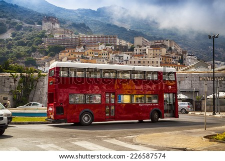 Gibraltar,  British Overseas Territory - JULY 11, 2013: Red bus on the street at the foot of Gibraltar rock. Entrance to Casemates Square. - stock photo