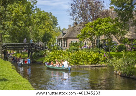 "GIETHOORN, NETHERLANDS - AUGUST 05 2013: Unknown visitors in the sightseeing boating trip in a canal in Giethoorn. The beautiful houses and gardening city is know as ""Venice of the North""."